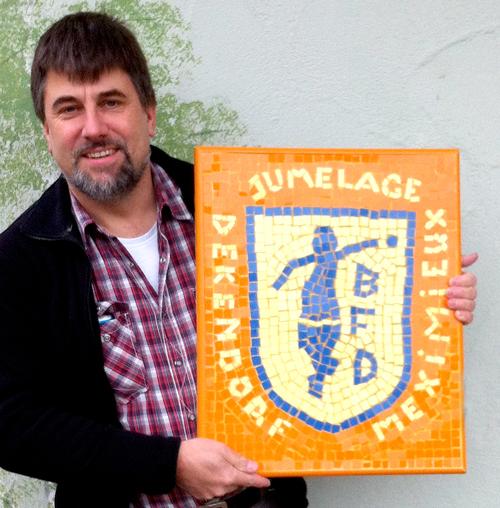 Der Denkendorfer Vereinsvorsitzende Frank Naumann mit einem Partnerschaftsgeschenk, das die Association de Pétanque de Meximieux bei einem örtlichen Mosaikkünstler hatte anfertigen lassen.